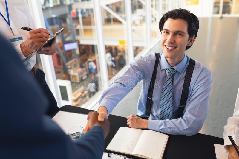 Gente di affari che stringe le mani a vicenda mentre controllando alla tavola di registrazione di conferenza immagini stock
