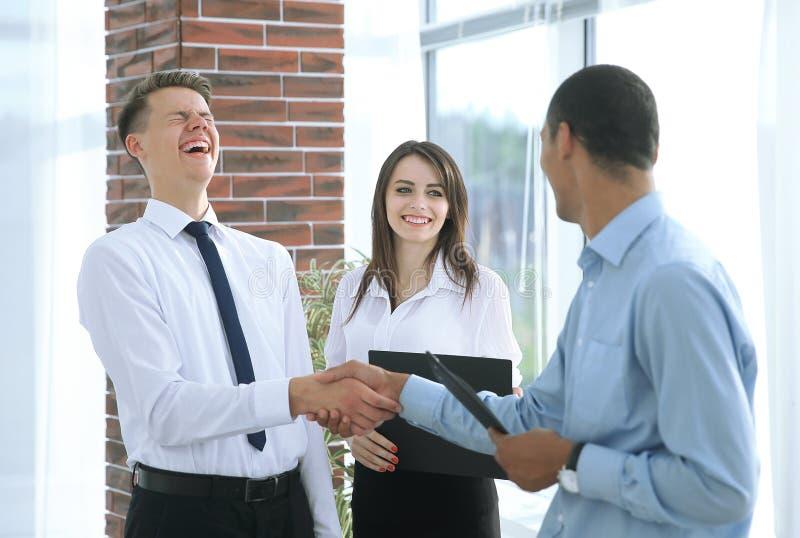 Gente di affari che stringe le mani a vicenda nell'ufficio fotografia stock libera da diritti