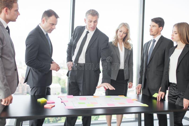 Gente di affari che sviluppa piano sulla scrivania fotografia stock