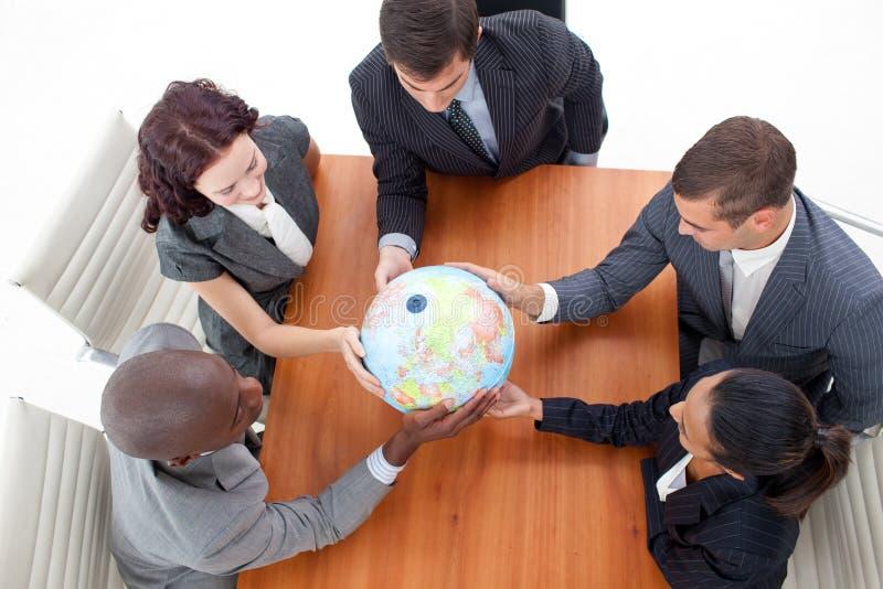 Gente di affari che tiene un globo fotografia stock