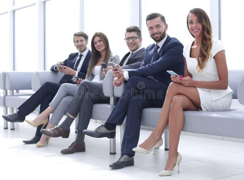 Gente di affari con i telefoni cellulari che si siedono nel corridoio luminoso fotografia stock libera da diritti
