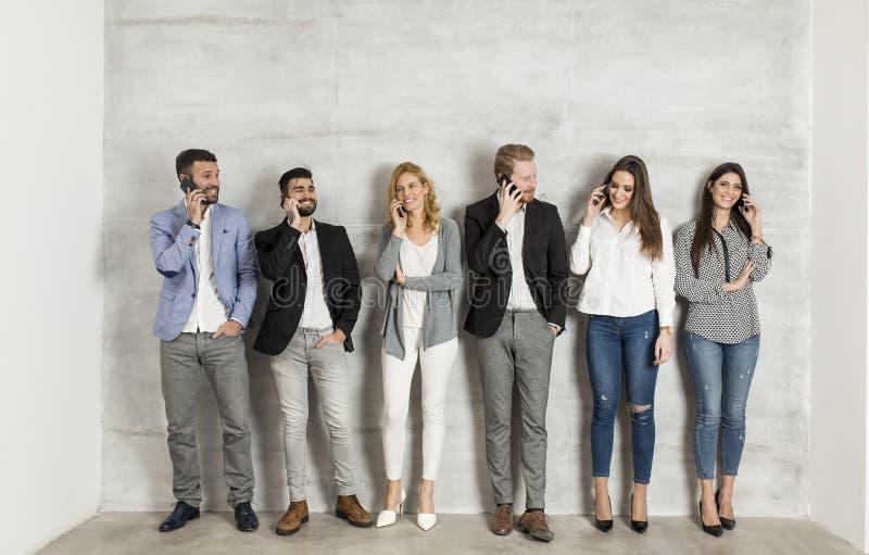 Gente di affari con il telefono cellulare che fa una pausa la parete immagine stock libera da diritti