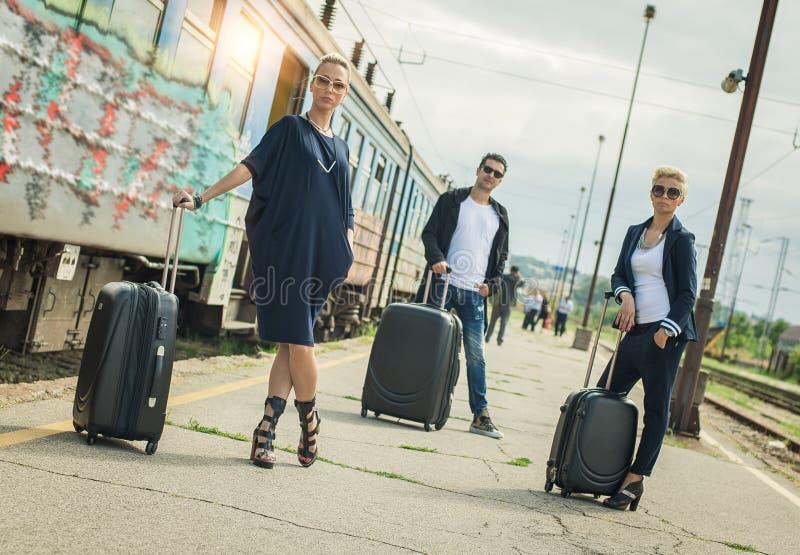 Gente di affari con la valigia che posa sulla stazione ferroviaria fotografia stock