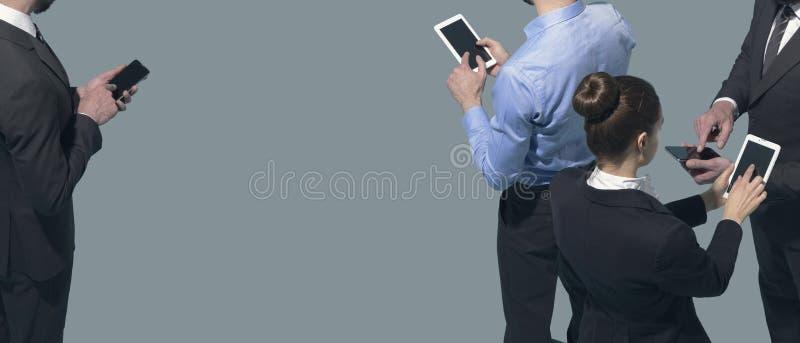 Gente di affari corporativa che incontra e che per mezzo degli smartphones immagine stock