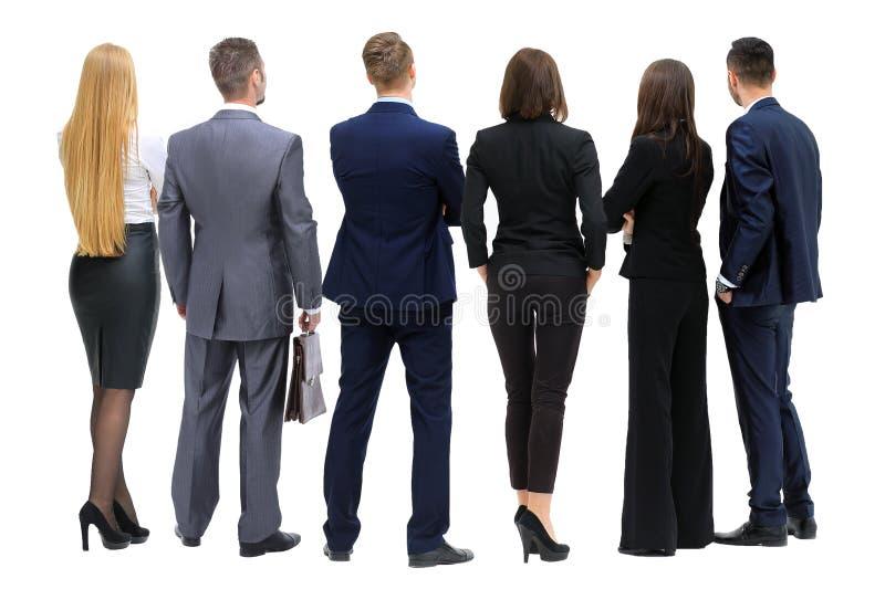 Gente di affari dal retro- esaminando qualcosa sopra un briciolo fotografia stock