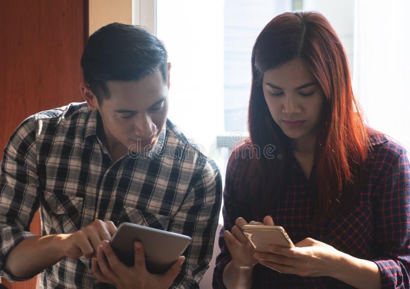 Gente di affari del cellulare della compressa commovente nella riunione d'affari immagine stock