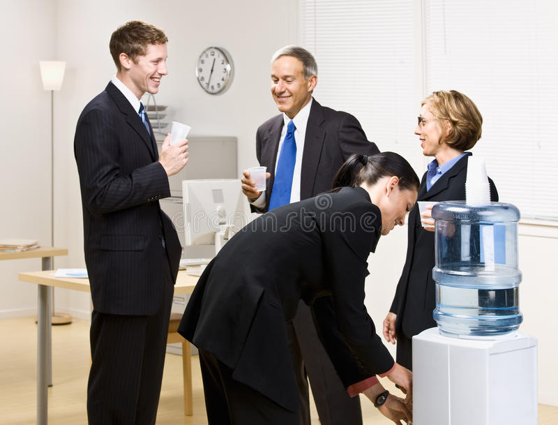 Gente di affari dell'acqua potabile al dispositivo di raffreddamento di acqua immagini stock