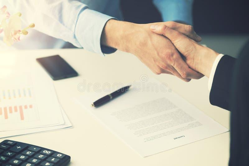 Gente di affari della stretta di mano dopo la firma del contratto di partenariato immagini stock