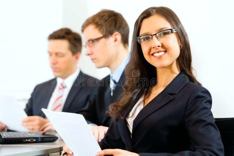 Gente di affari durante la riunione nell'ufficio immagine stock libera da diritti