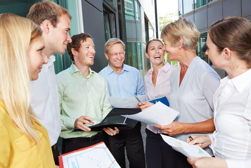 Gente di affari felice che parla fuori dell'ufficio immagine stock