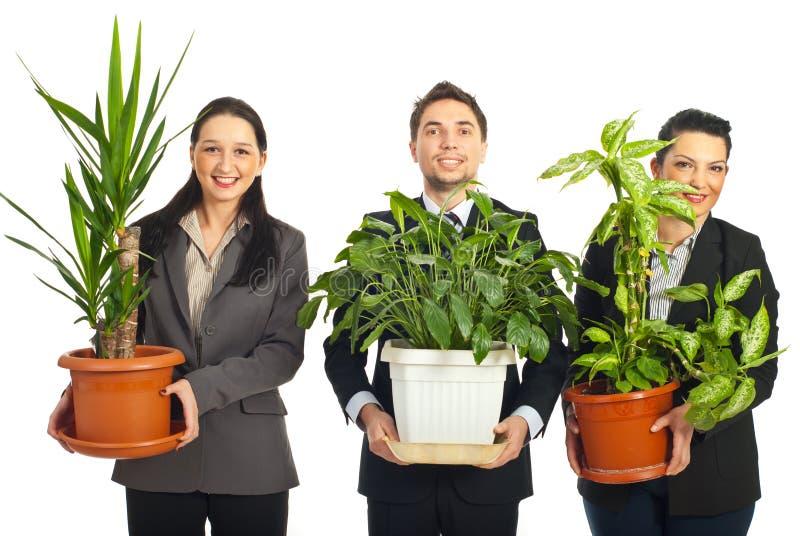 Gente di affari felice che tiene i vasi con le piante immagini stock libere da diritti