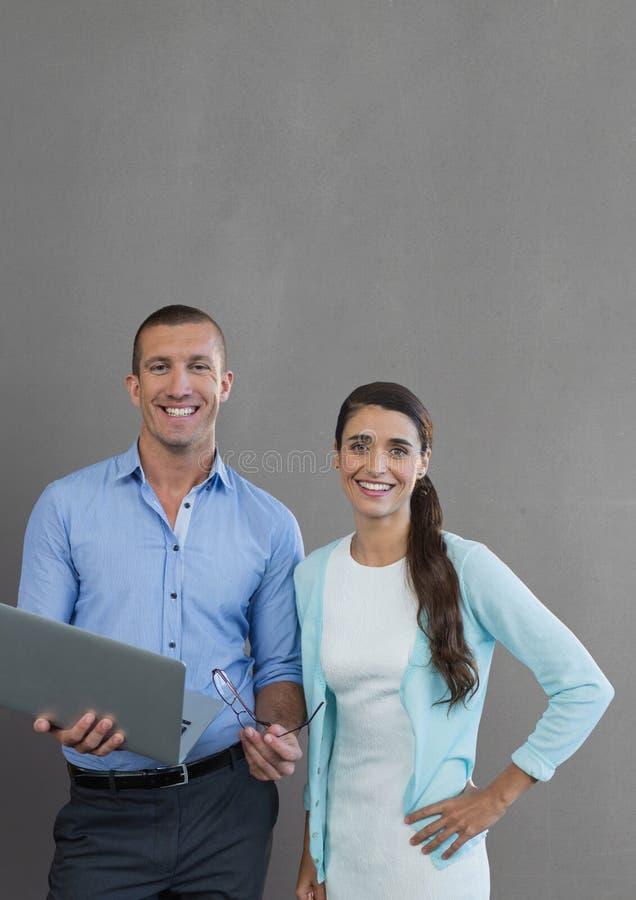 Gente di affari felice che tiene un computer contro il fondo grigio fotografia stock