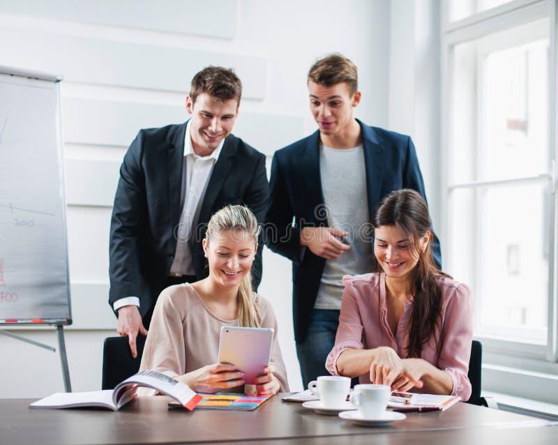 Gente di affari felice che utilizza il PC della compressa allo scrittorio nell'ufficio immagini stock libere da diritti