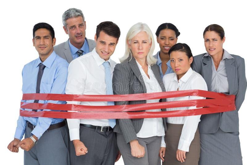 Gente di affari infelice che circonda dalla striscia rossa fotografia stock