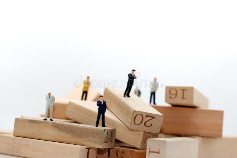 Gente di affari miniatura che si siede sul blocco di legno, assunzione e fotografia stock libera da diritti