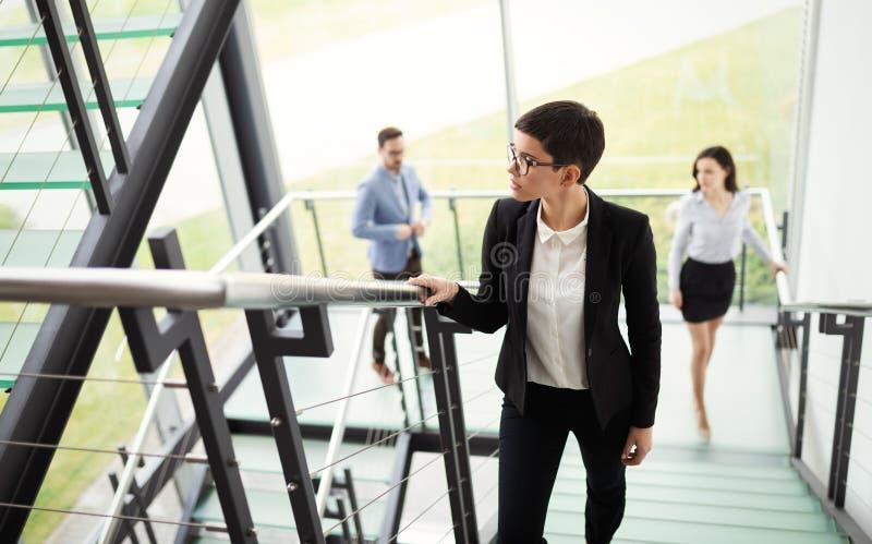 Gente di affari moderna che cammina sulle scale in corridoio di vetro nell'edificio per uffici fotografia stock