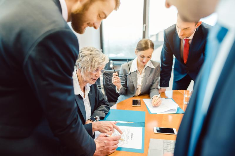 Gente di affari nell'ufficio durante la riunione discutendo una transazione fotografia stock libera da diritti