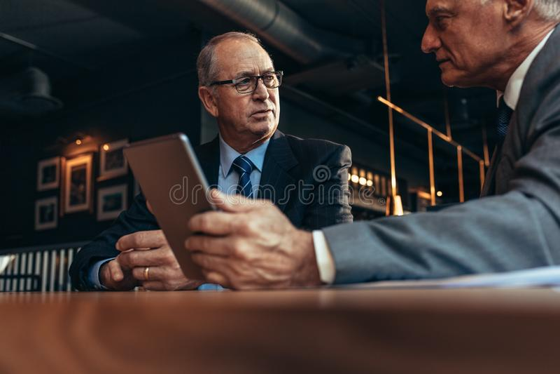 Gente di affari senior che si incontra al ristorante moderno immagini stock