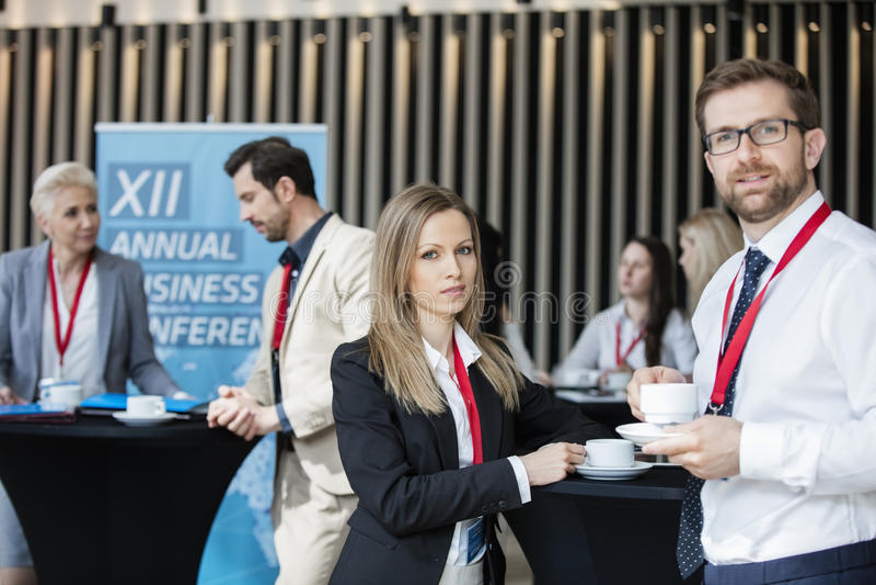 Gente di affari sicura che tiene le tazze di caffè all'ingresso nel centro di convenzione immagine stock libera da diritti