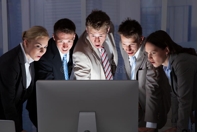 Gente di affari sorpresa che esamina il monitor del computer immagini stock