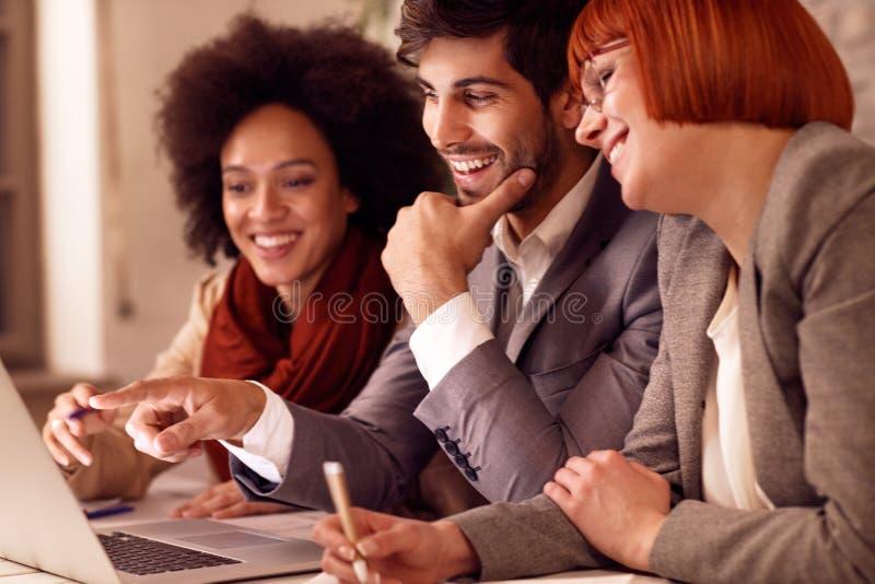 Gente di affari sorridente che confronta le idee sulla riunione immagine stock libera da diritti
