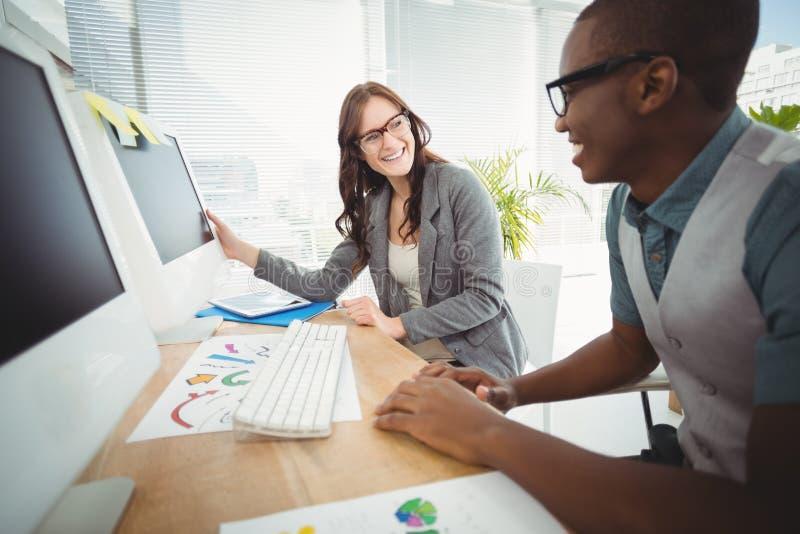 Gente di affari sorridente che indossa gli occhiali che funzionano allo scrittorio del computer fotografie stock libere da diritti