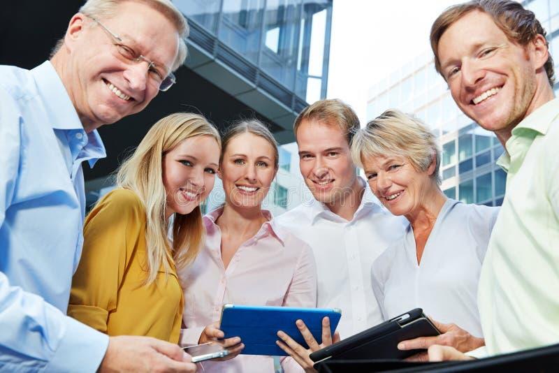 Gente di affari sorridente con il computer della compressa fotografia stock libera da diritti