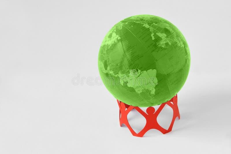 Gente di carta in un cerchio che tiene il globo della terra verde - raggiro di ecologia immagini stock