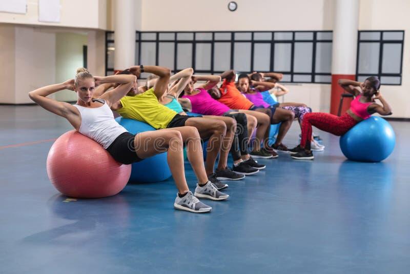 Gente di formazione dell'istruttore femminile per eseguire yoga sulla palla di esercizio fotografia stock