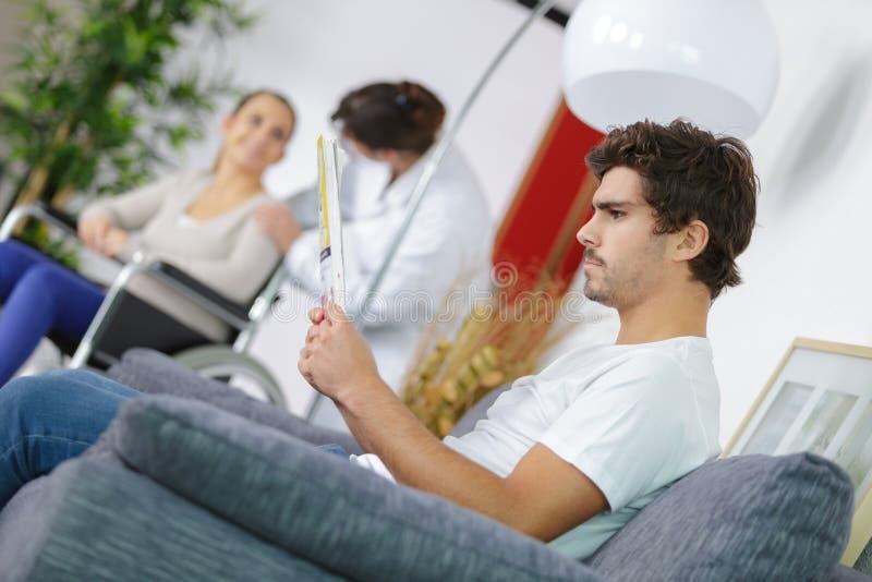 Gente differente che si siede nell'ospedale della sala di attesa fotografia stock