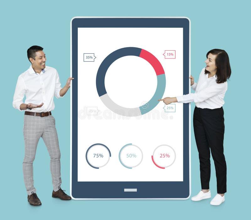 Gente diversa alegre que muestra el gráfico de sectores en una tableta imágenes de archivo libres de regalías