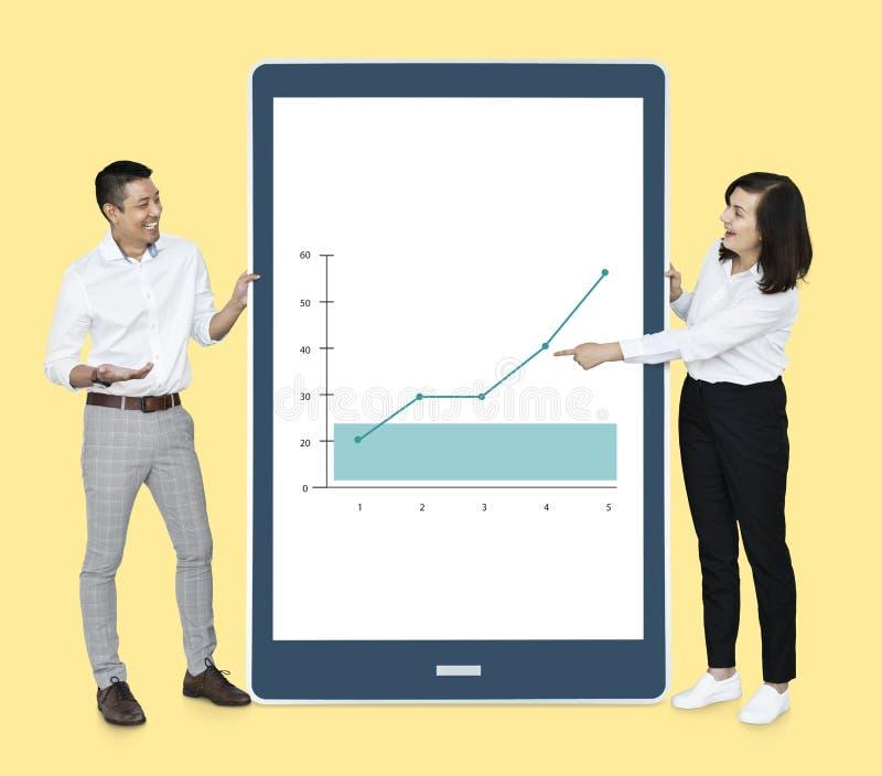 Gente diversa alegre que muestra un gráfico en una tableta foto de archivo