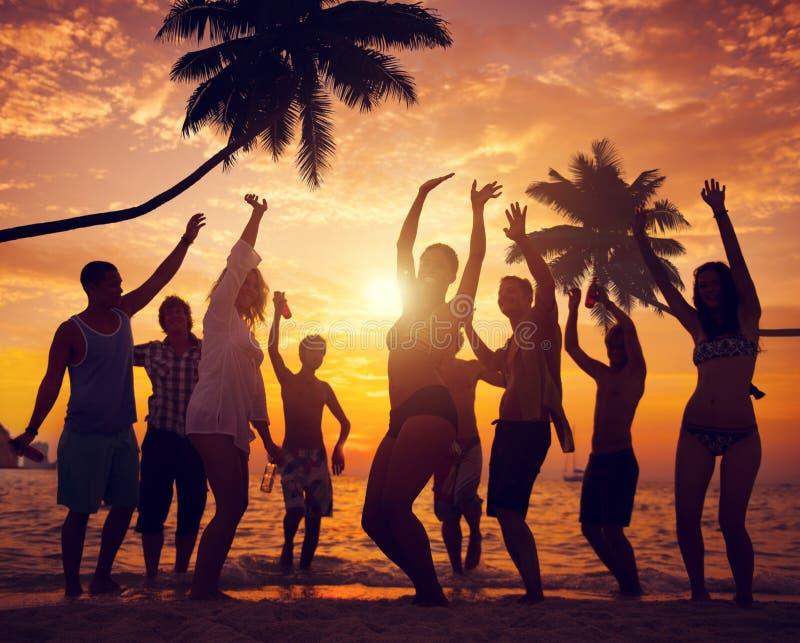 Gente diversa que baila y que va de fiesta en una playa tropical imagen de archivo