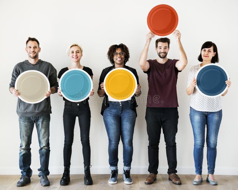 Gente diversa que lleva a cabo al tablero redondo en blanco foto de archivo