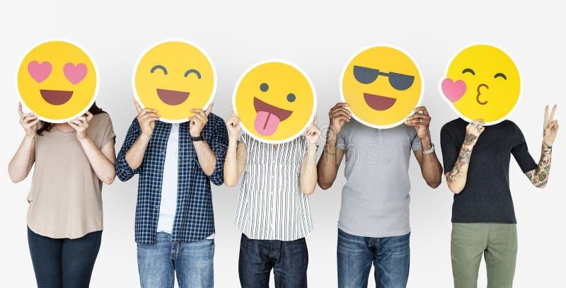 Gente diversa que sostiene emoticons felices imagen de archivo libre de regalías