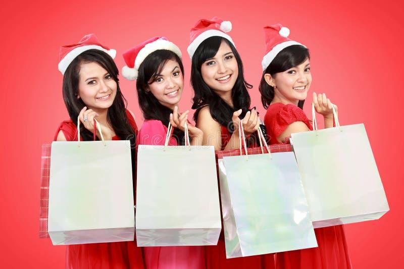 Gente divertida feliz con el sombrero de santa de la Navidad que sostiene las cajas de regalo a fotos de archivo