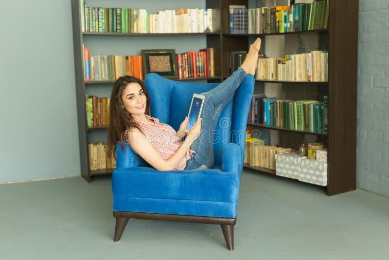 Gente, educación y concepto interior - estudio del estudiante en biblioteca escolar en silla fotografía de archivo