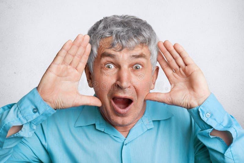 Gente, emociones y concepto de las expresiones faciales El viejo varón maduro sorprendente ha fastidiado ojos y mantiene la boca  imagen de archivo libre de regalías
