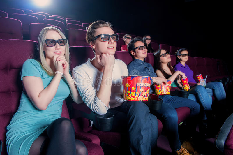 Gente en el cine que lleva los vidrios 3d imagen de archivo libre de regalías