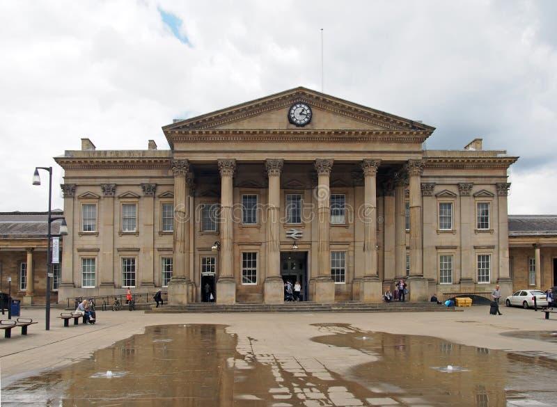 gente en el cuadrado Huddersfield de Jorte del santo delante de la fachada de la estación de tren victorian histórica fotos de archivo
