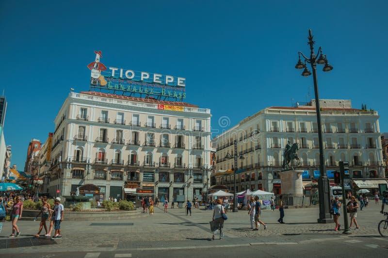 Gente en el del Sol Square de Puerta con los edificios en Madrid imágenes de archivo libres de regalías