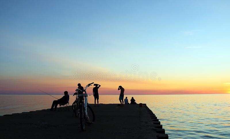 Gente en el embarcadero en Kincardine, Ontario en la puesta del sol imagen de archivo