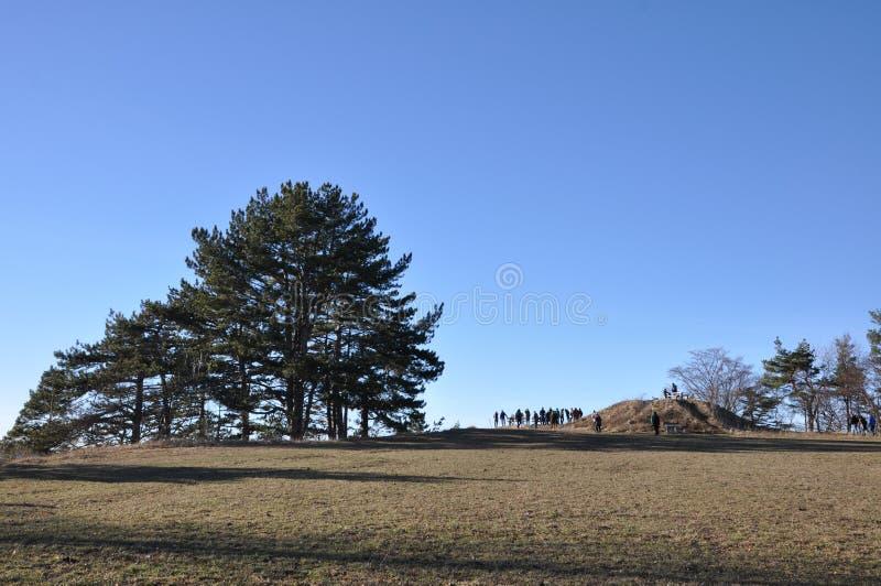 Gente en el poste de la perspectiva en el top de la montaña foto de archivo