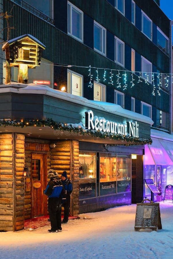 Gente en el restaurante tradicional en el invierno Rovaniemi iluminado en la noche fotos de archivo libres de regalías