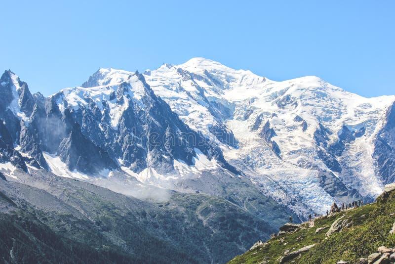 Gente en el top de un soporte que sorprende de desatención Blanc de la roca, cerca de Chamonix en las montañas francesas El pico  fotografía de archivo libre de regalías