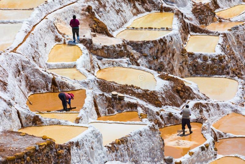 Gente en el trabajo en los saltpans de Moray Peru foto de archivo