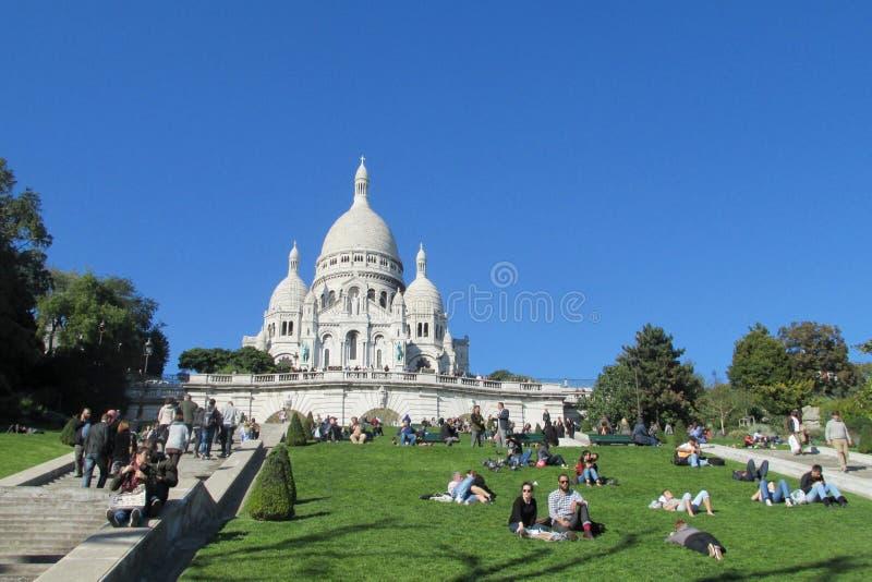 Gente en hierba cerca de la basílica del corazón sagrado de París en Montmartre imagen de archivo