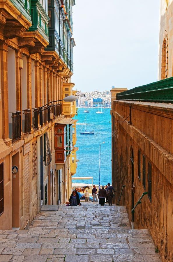 Gente en la calle de La Valeta con la ciudad de Gzira en el puerto magnífico fotos de archivo