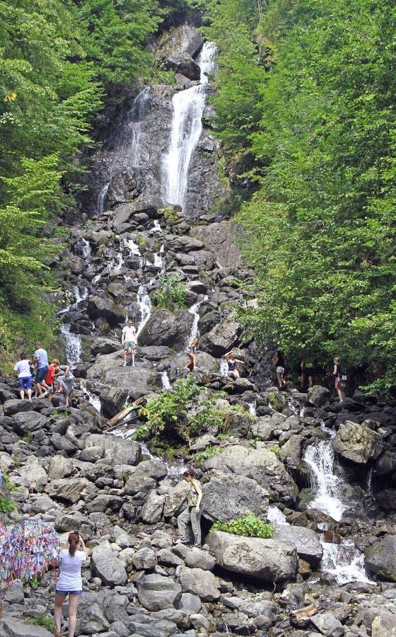 Gente en la cascada lechosa en Abjasia imagen de archivo
