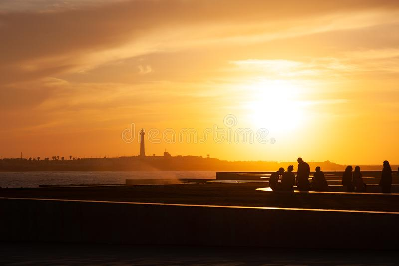 Gente en la costa en Marruecos en la puesta del sol imagen de archivo libre de regalías